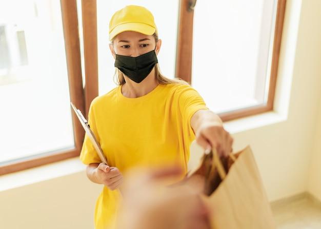 Женщина доставки среднего выстрела, держащая сумки