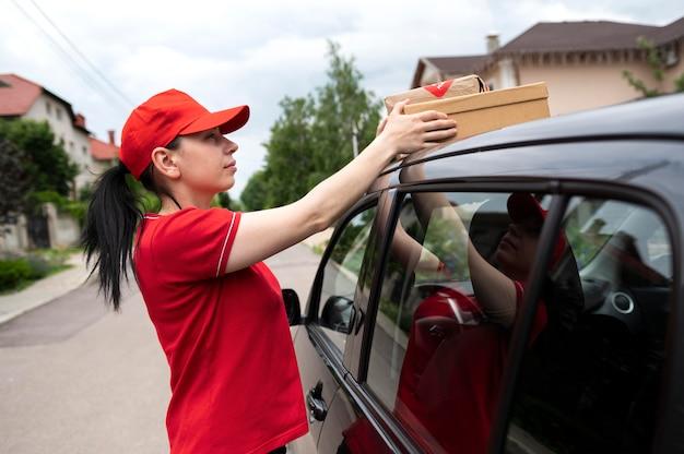 Женщина доставки среднего выстрела, держащая пакет