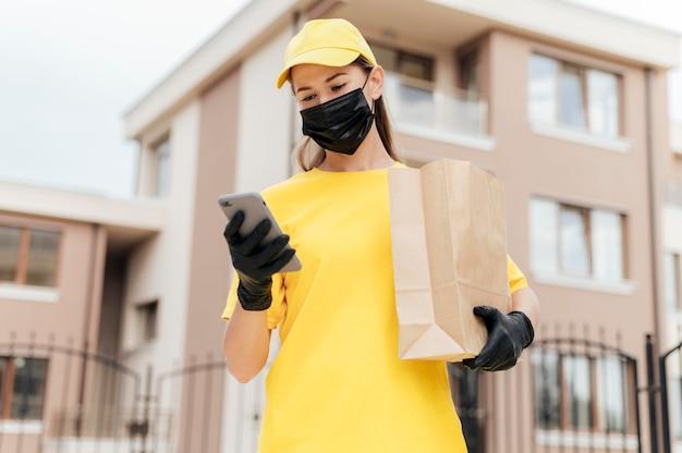 Donna di consegna colpo medio con borsa