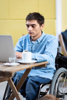 Medium shot disabled man working on laptop
