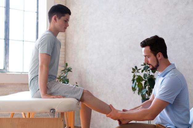 소년의 다리를 확인하는 중간 샷 의사