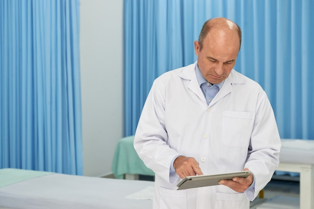 Medium shot of doctor checking medical history on digital pad device