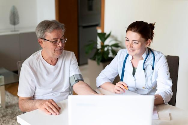 Medico a colpo medio che controlla paziente