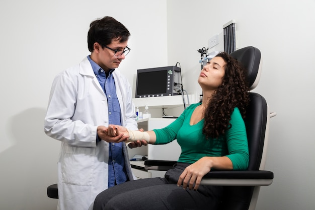 Medium shot doctor examining bandaged arm