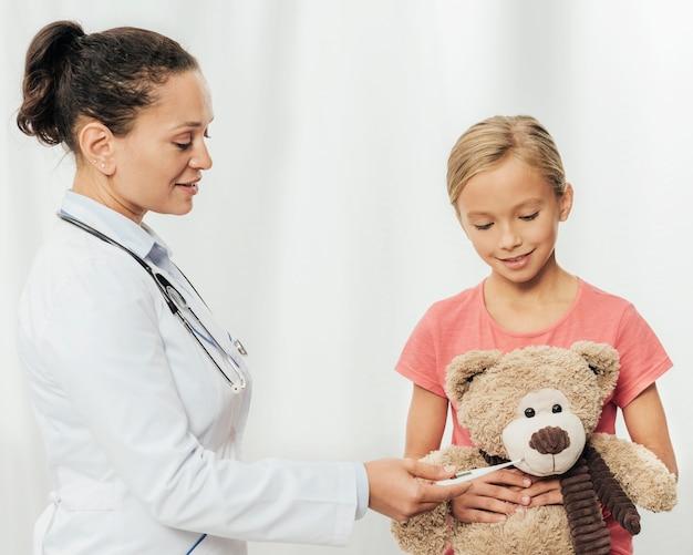 Medico e ragazza del colpo medio con l'orso