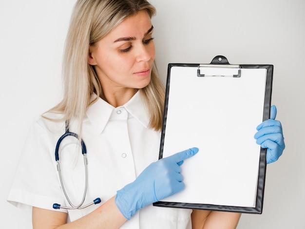 Medium shot doctor holding clipboard