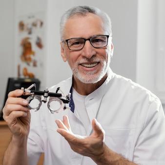 Medium shot doctor holding eye examination glasses