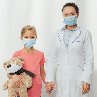 Colpo medio medico e bambino che tengono le mani