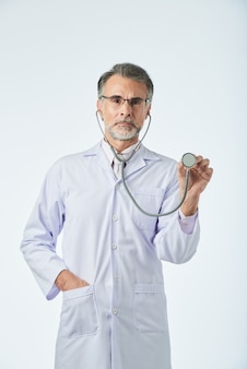 Medium shot of doctor looking at camera and gesturing with stethoscope as if checking the heartbeat