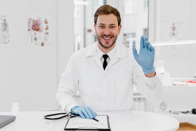 手袋をはめたミディアムショットの医者