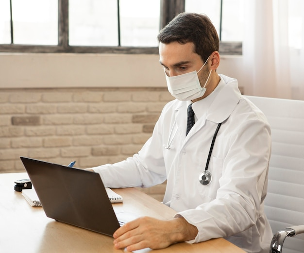 マスクを身に着けているミディアムショットの医者