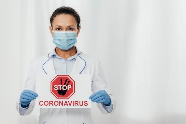 Medium shot doctor with coronavirus sign