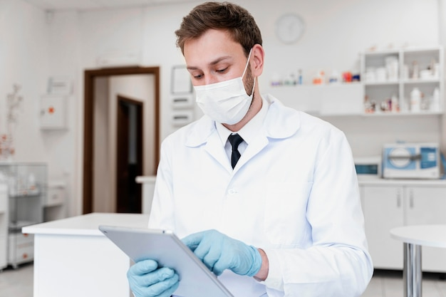 Medium shot doctor with mask and tablet