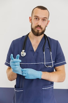 Medium shot doctor with stethoscope and gloves