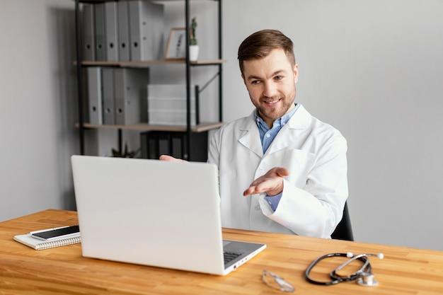 Medico del colpo medio che lavora alla scrivania