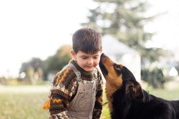 ミディアムショットの犬が子供にキス