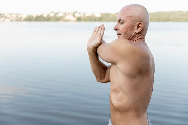 Medium shot elder stretching near lake