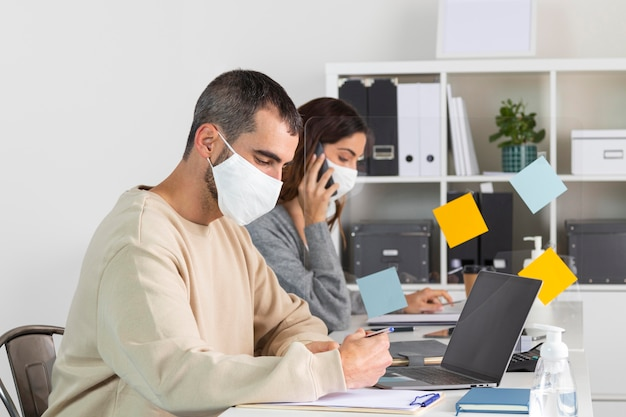 Medium shot employees with mask