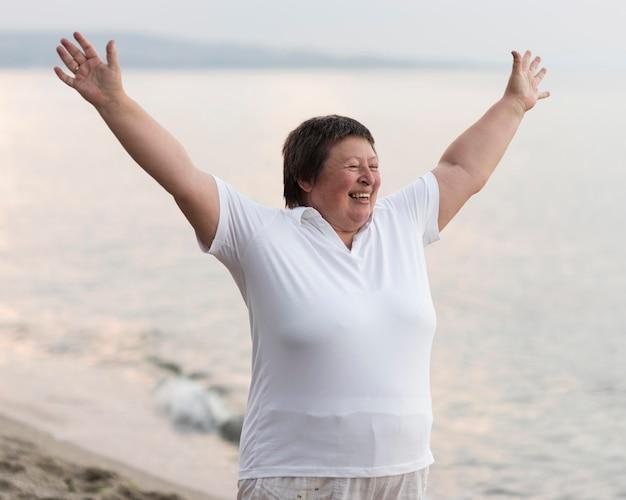 Donna emozionante del colpo medio alla spiaggia