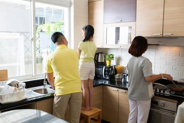 ミディアムショットの家族が一緒に料理する