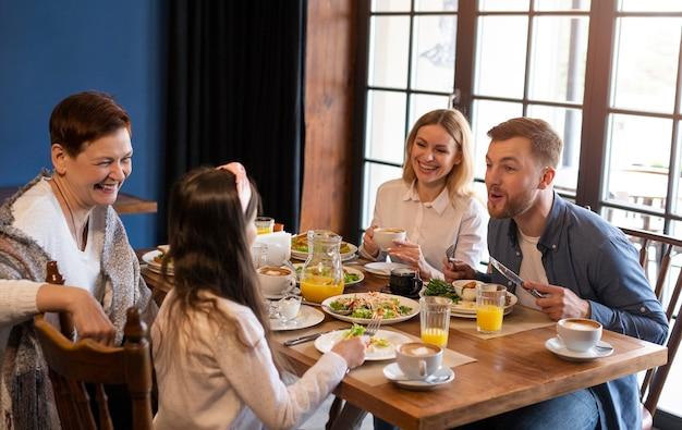 Семья среднего размера, едящая вместе