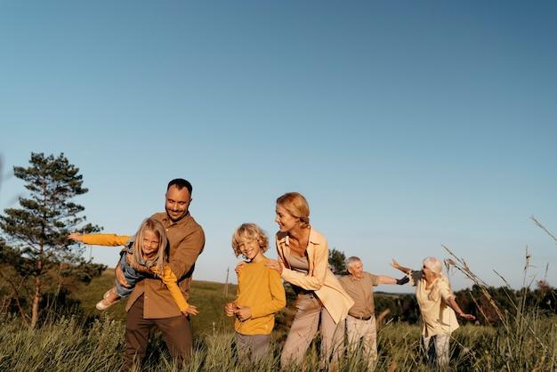 Medium shot family having fun on meadow