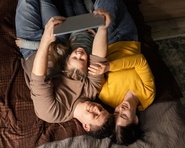 ベッドに横たわっているミディアムショットの家族