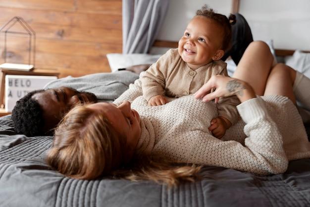 ベッドの上で子供と一緒に横たわっているミディアムショットの家族