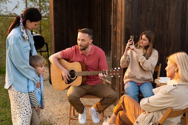 ギタープレーヤーを聴いているミディアムショットの家族