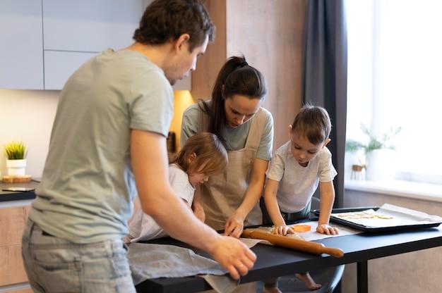 ミディアムショットの家族がクッキーを作る