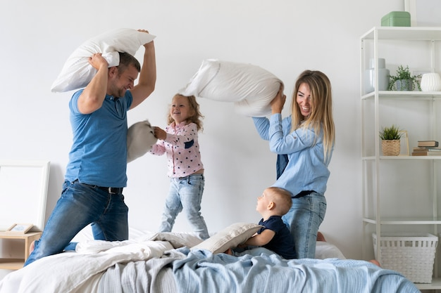 Medium shot family members fighting with pillows