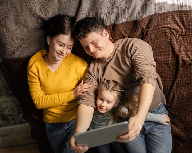 ベッドに座っているミディアムショットの家族