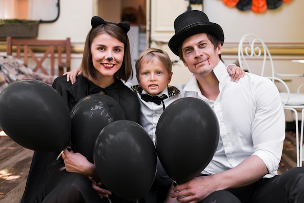 Medium shot family with black balloons