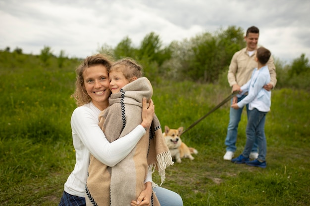 屋外で犬とミディアムショットの家族
