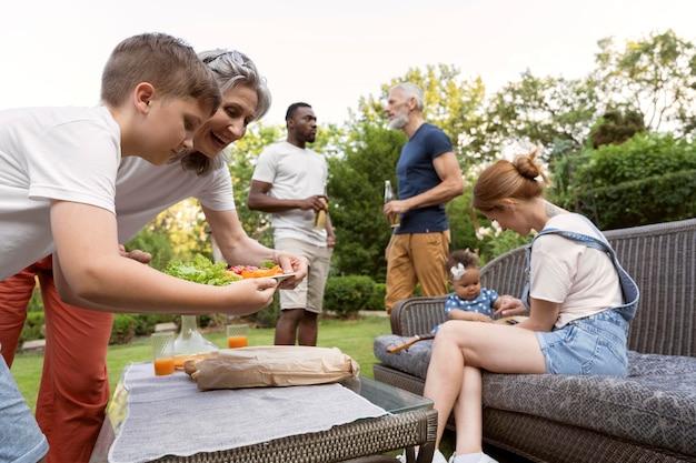 Famiglia a ripresa media con cibo all'aperto
