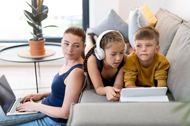 Famiglia a ripresa media con laptop sul divano