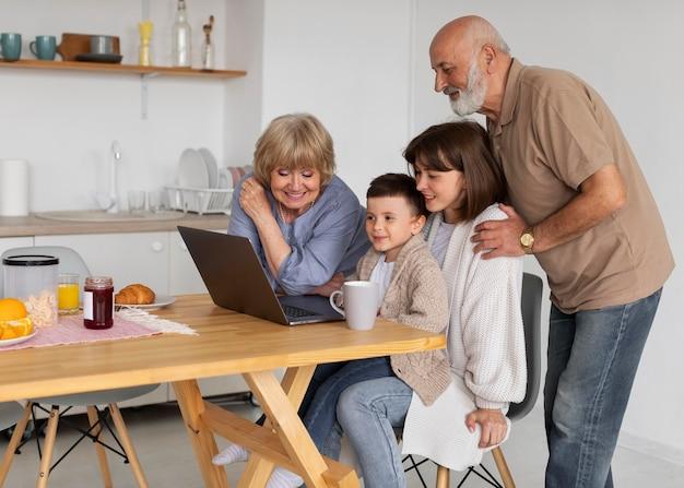 ノートパソコンを搭載したミディアムショットの家族