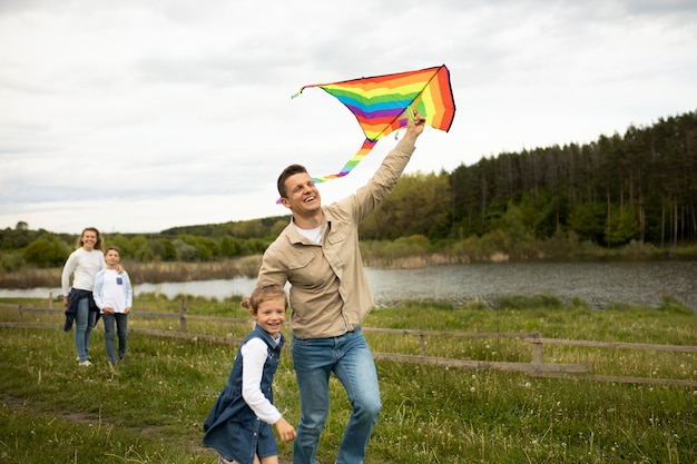 Famiglia a tiro medio con aquilone arcobaleno