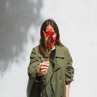 Medium shot fashion woman covering her face with bunch of peppers