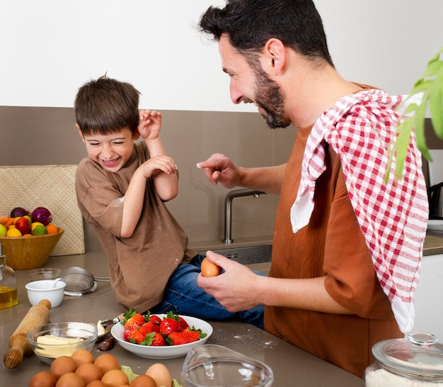 ミディアムショットの父と少年が一緒に料理をする