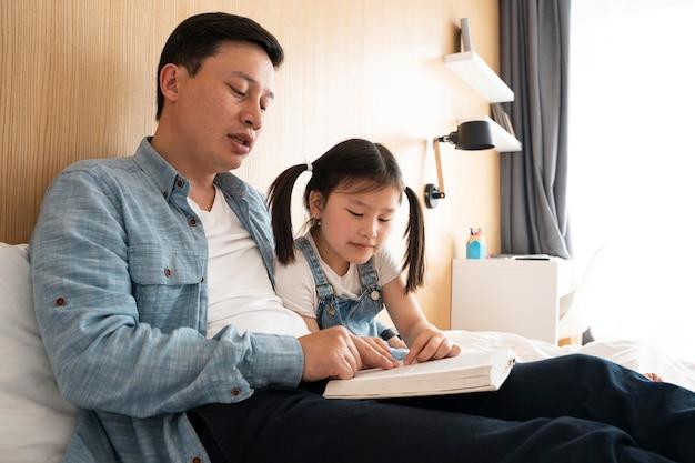 중간 샷 파더 및 여자 아이 독서 모드 프리미엄 사진