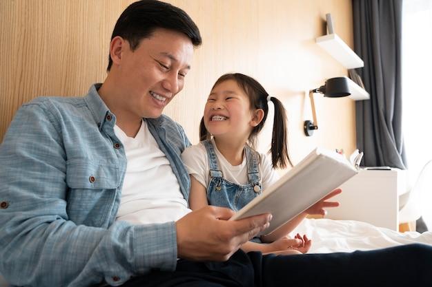 Средний план отец и девочка с книгой