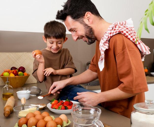 ミディアムショットの父と子供が一緒に料理する