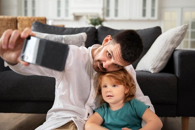 Средний снимок отца и ребенка, делающих селфи
