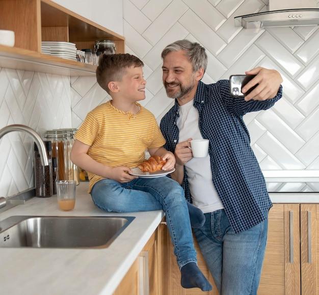 ミディアムショットの父と子供が自分撮りをしている