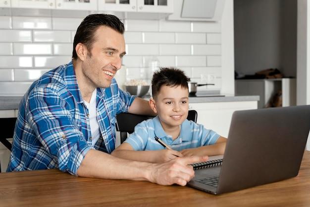 중간 샷 아버지와 아이 노트북
