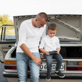 Средний снимок отца и ребенка со смартфоном