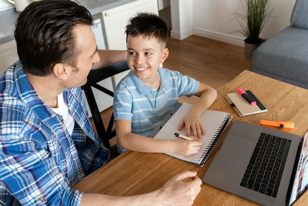 Medium shot father and boy with laptop