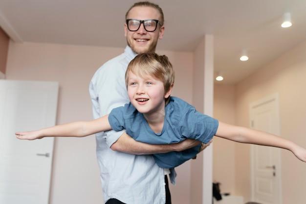 ミディアムショットの父親が男の子を抱いている