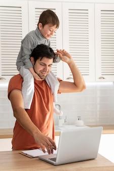 子供を抱いて働いているミディアムショットの父